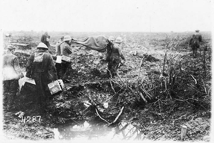 Prisoners bringing in wounded in the early morning. Passchendaele. 1917.