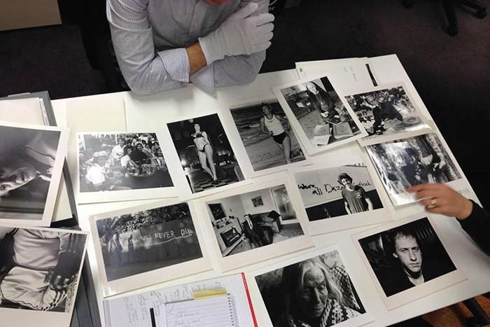 The exhibition team select images from one of Robin Morrison's image folders which he labelled 'Decade of Days.'
