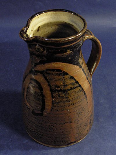 The dark tenmoku glaze on this stoneware jug is often found in Japanese and Chinese ceramics.
