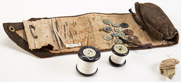 Military sewing kit made of brown suede and containing reels of cotton, buttons, thread and needles.