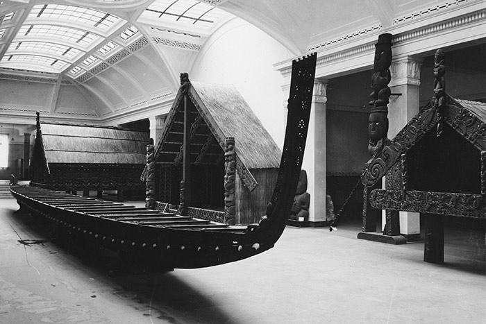 View of the Māori Court, lit by skylight. The waka is in the foreground, with Hotunui behind it, the storehouse Te Oha to the right, and the large pataka Te Puawai o te Arawa in the background. The tall carving Te Rangitakaroro is against a pillar next to Te Oha.