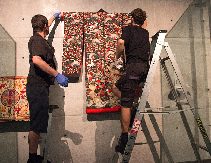 Display technicians Chris Sheehan and Charlie Charlick installing a Japanese Furisode robe (object number:  T1048).