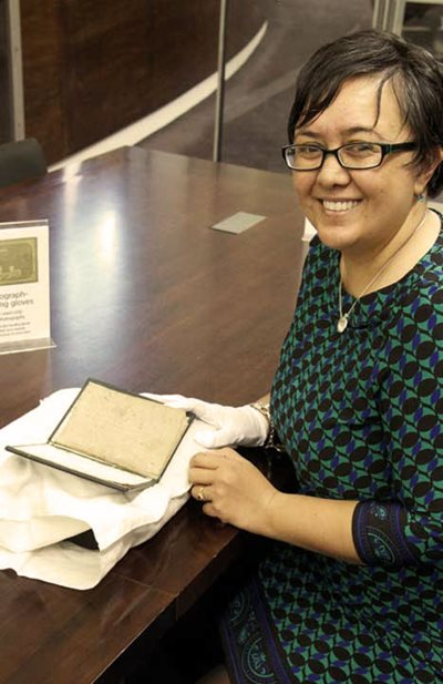 Linnae Pohatu holds A korao no New Zealand, or, The New Zealander\u0027s first book: being an attempt to compose some lessons for the instruction of the natives by Thomas Kendall, 1815.