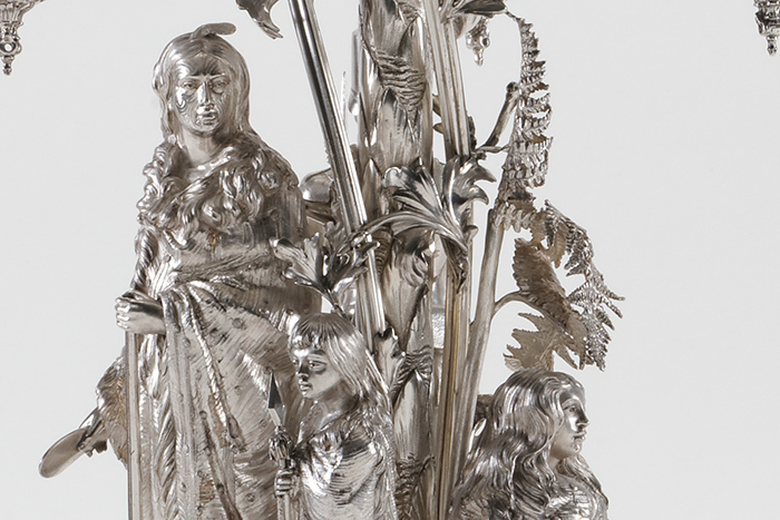 The epergne depicts a Māori family ​underneath a native New Zealand tree​.​