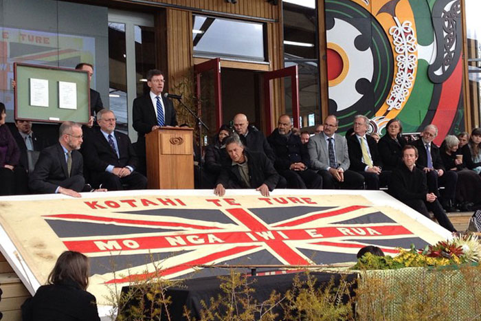 The Maungapōhatu flag is unfurled for the crowds at Taneatua as the Hon. Christopher Finlayson makes his address to Tūhoe.