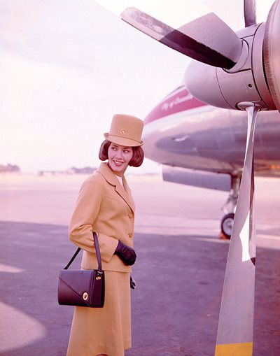 This glamorous NAC air hostess uniform was designed in 1965 by Barbara Penberthy of Babs Radon. The outfit, made from wool barathea dyed a golden topaz colour, was known as the \u0027Golden Cloud\u0027.
