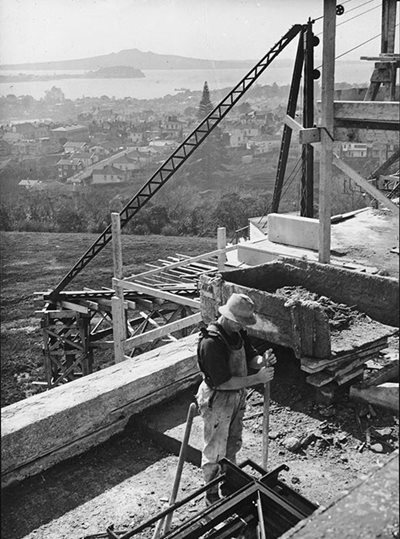 Workman on the Museum roof during construction. Rangitoto and North Head can be seen in the distance.