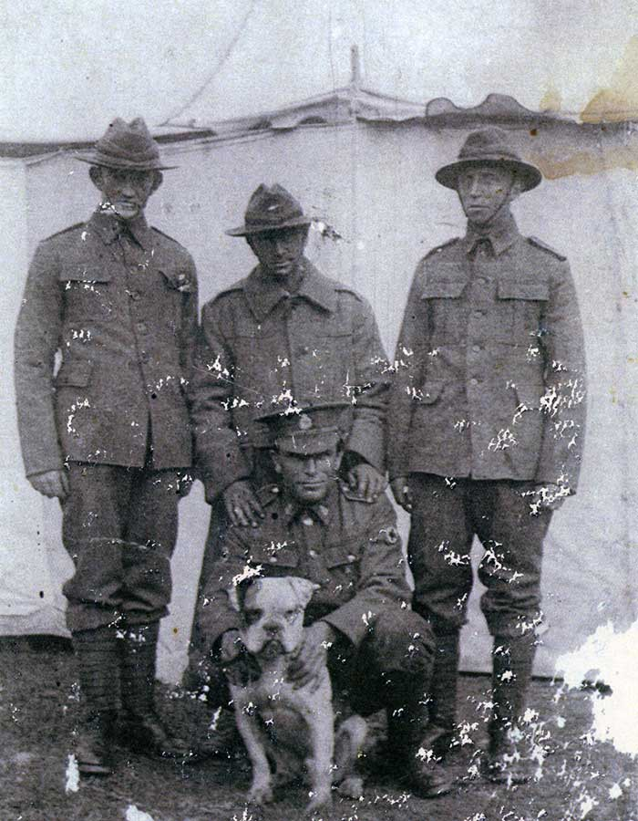 Photograph of Rifleman Thomas Samuel Tooman (s/n 26/918), Caesar\u0027s handler, standing on left and Caesar, being held by Private Albert Edward Griffin (s/n 3/1513).
