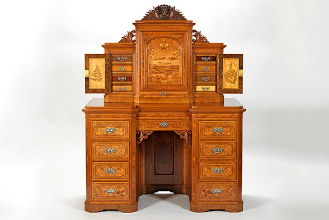 The Baden-Powell Desk. Production date:  1903, Auckland. Primary maker:  William Seuffert. Materials: Native woods including, burr tōtara, kauri, rewarewa, pūriri, and kohekohe Method: Marquetry and parquetry (inlaying wood pieces to make images and geometric shapes).